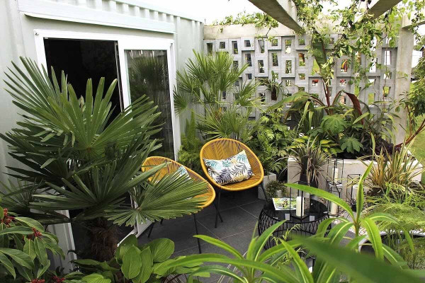 Basalt porcelain seating area with bright yellow chairs and cushions, a round coffee table all surrounded by exotic planting.***Designed by Sara Edwards at No.30 Design Studio, Built by Design It Landscapes