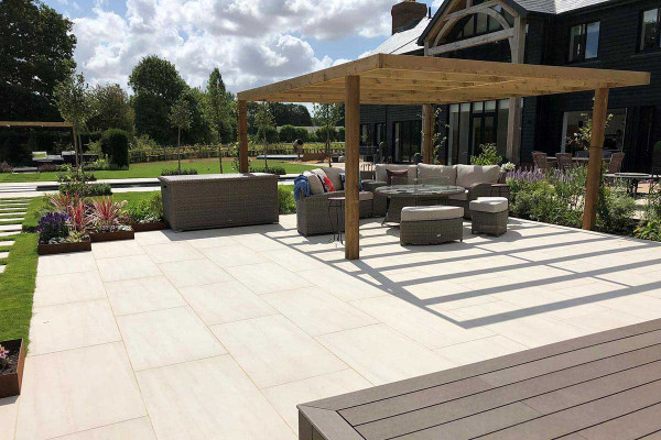 Impressive garden space paved with Faro Porcelain Paving that has luxury rattan garden furniture under a large wooden pergola.***Designed by Rachel Goozee Garden & Planting Design, www.rachelgoozee.com   Built by Wilkinson Landscapes Sussex Ltd