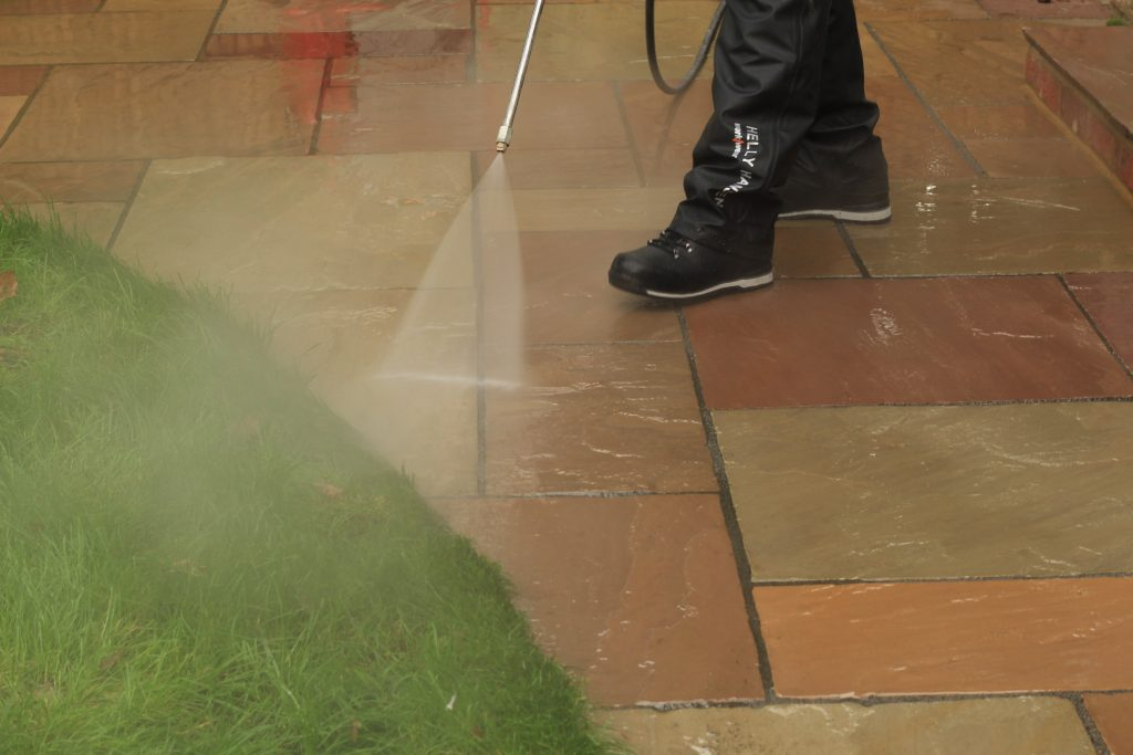 A jetwash set on medium pressure with fantail setting, held at 45 degree angle, to show the correct method of jetwashing to preserve the pointing in the paving, from London Stone
