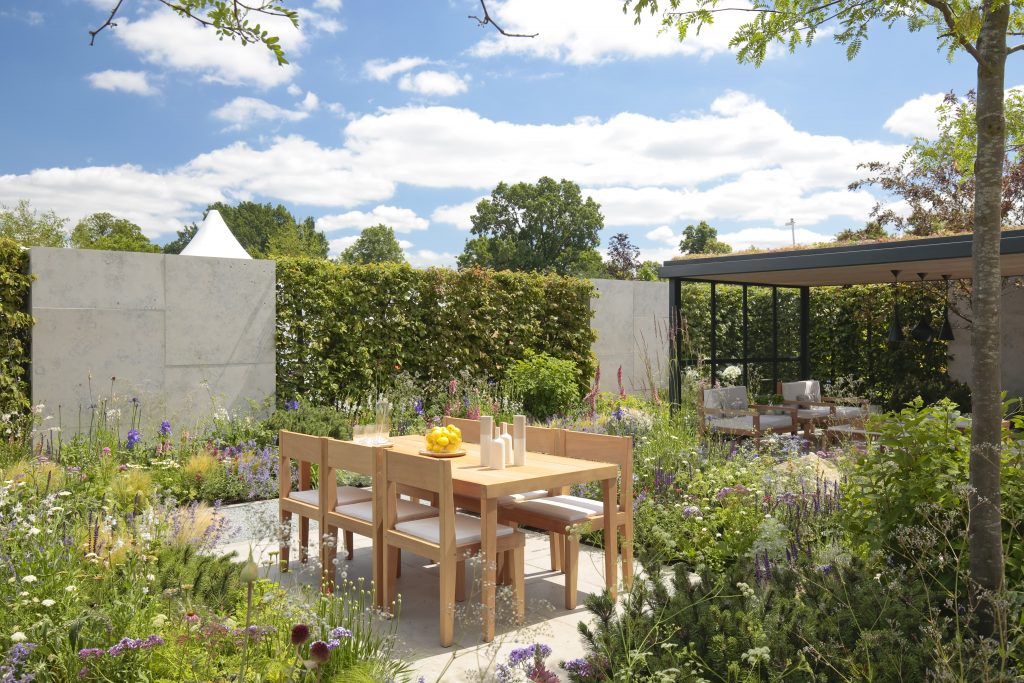 Hedging is paired with stone walling to soundproof this peaceful garden with wooden seating and plenty of planting.