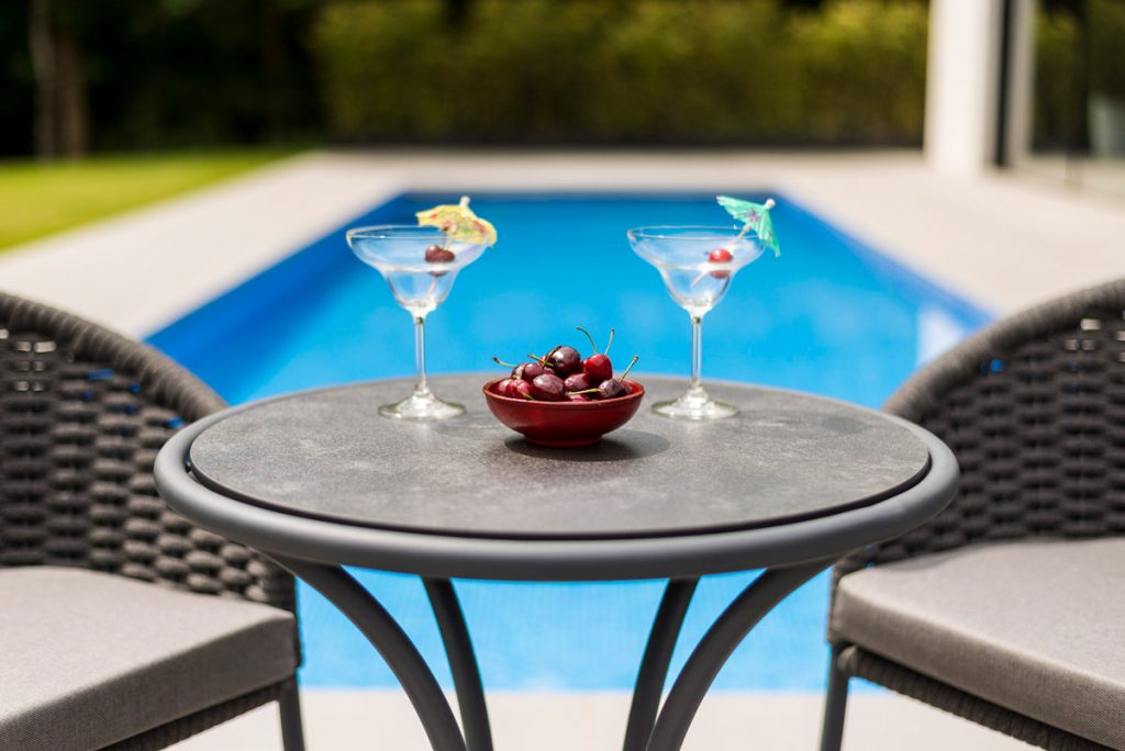 Rattan Bistro Set from London Stone in front of swimming pool
