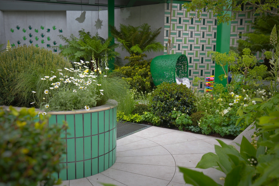 Florence Grey Porcelain is paired with green walling and seating and plenty of lush planting to make a bold contrast.