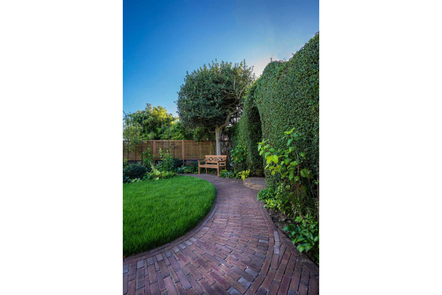 Thick hedging surrounds this garden to sound proof the space. Clay pavers edge the garden creating a pathway around the grass.