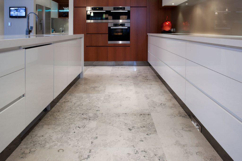 Create a modern kitchen with jura grey limestone tiles.
