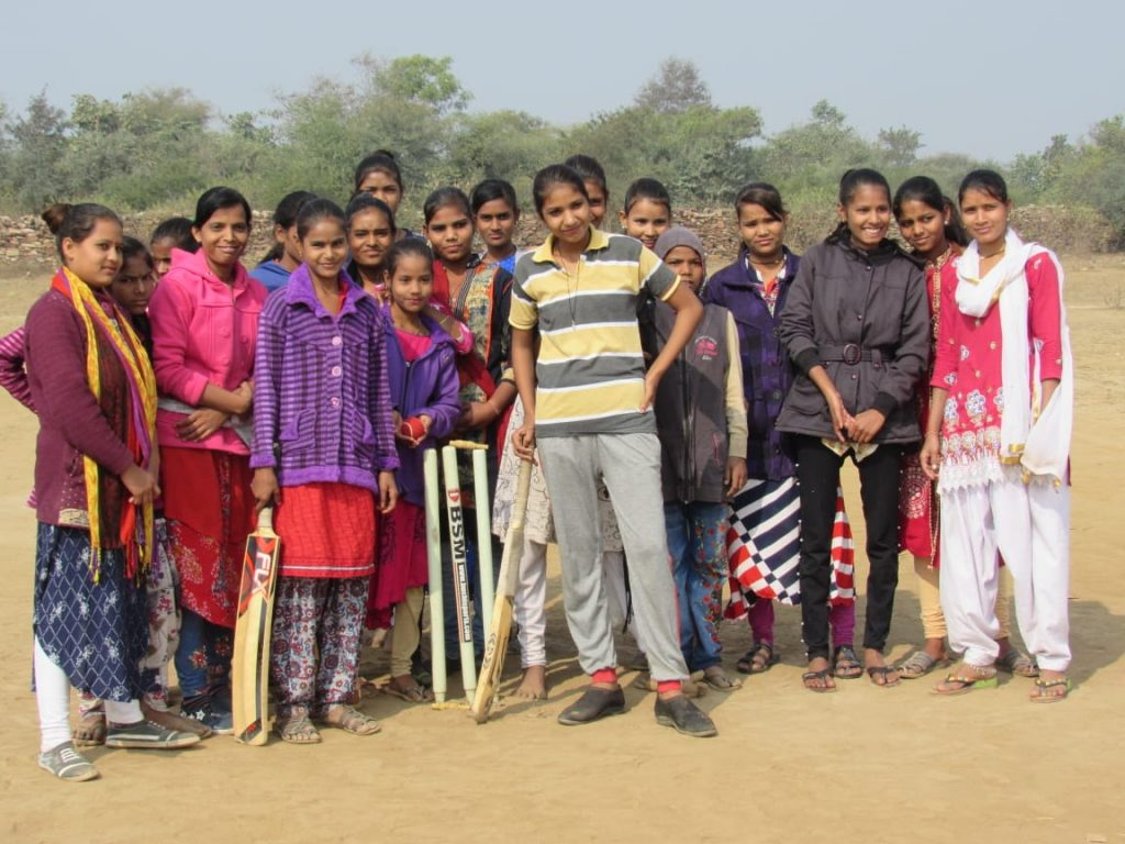 A girls' cricket team posing for the camera, in Budhpura, Rajasthan, India, No Child Left Behind