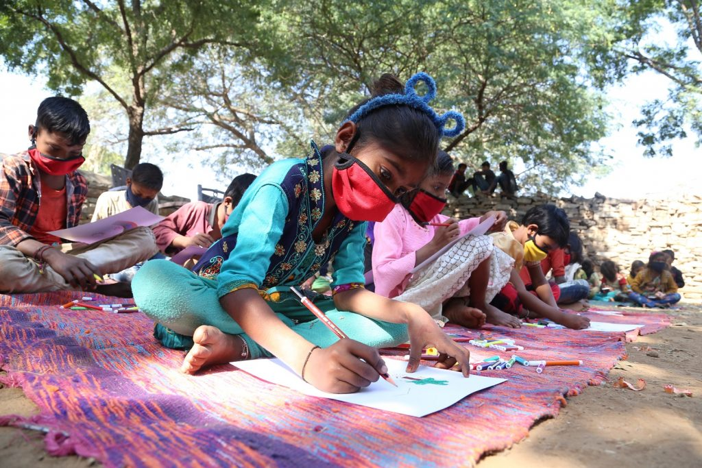A class of young children sitting on the ground in open air class, wearing masks, Rajasthan, India, No Child Left Behind