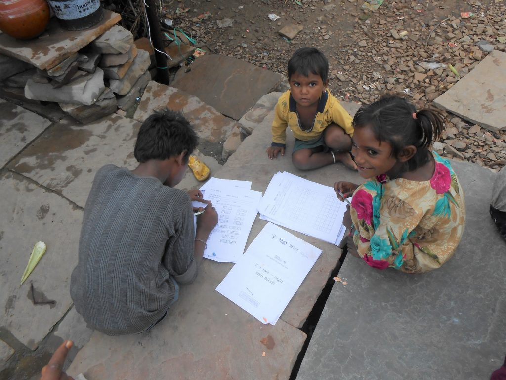 Group of 3 children of different ages, sitting on stone slabs, with worksheets spread around. in Budhpura, Rajasthan, India, No Child Left Behind