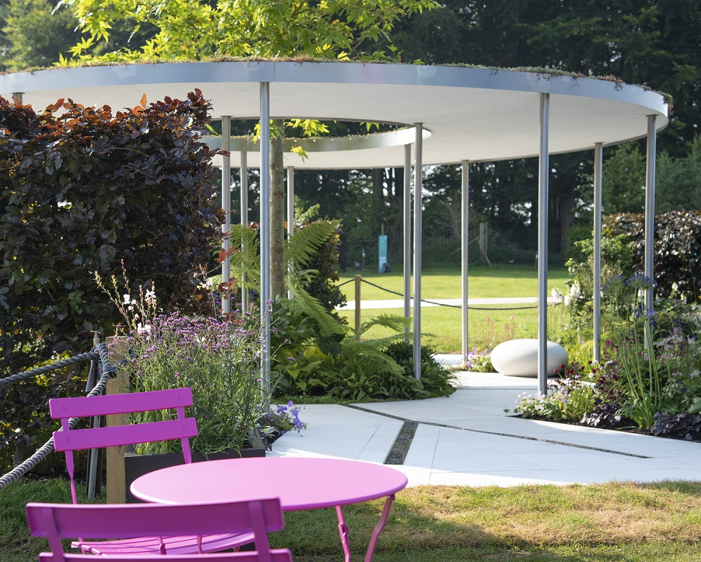 The Cancer Research Legacy Garden, RHS Tatton Park 2021, pink bisto set in foreground, white doughnut shaped roof with tree growing through hole, white paving with rills, designed Neil Sutcliffe, built Creative Roots, Florence White Porcelain, London Stone