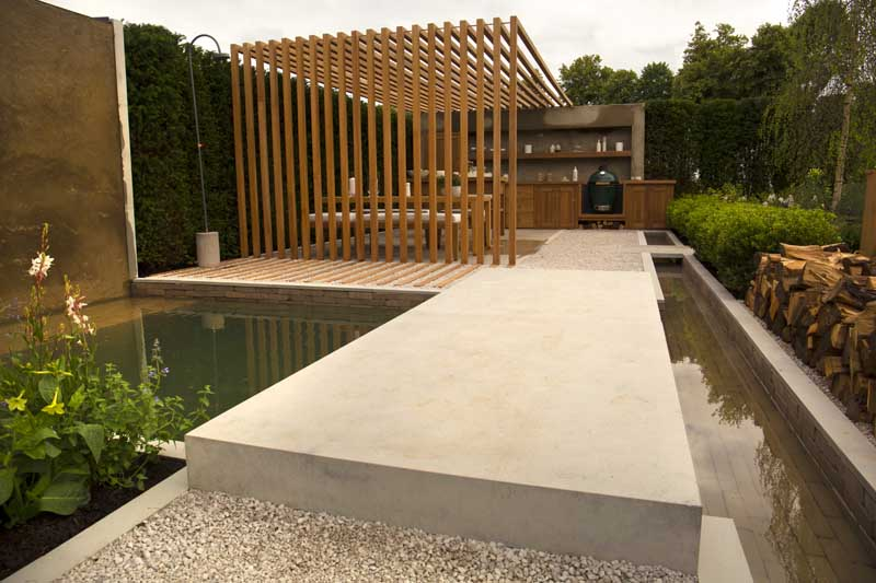 This bespoke Jura Grey Limestone bridge is paired with Gromo Antica clay pavers for a stunning result in this Hampton Court Palace Garden Festival 2021 garden.