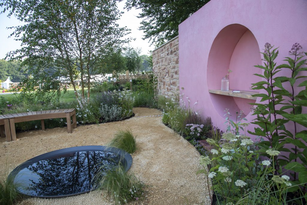The Dreamscape Garden has interesting circular shapes to symbolize the moon. Pastel tones throughout the garden are paired with the statement pink wall. At the base of the wall our Seville Clay Pavers make an interesting addition.