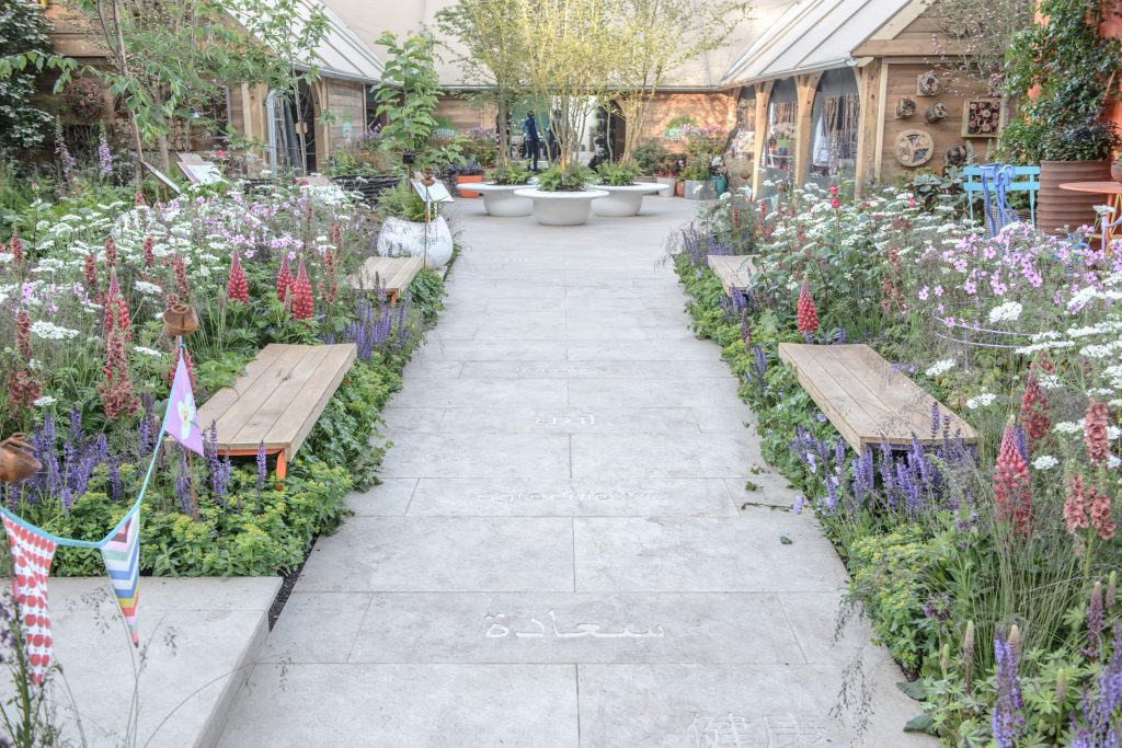 Golden Sand Porcelain Paving pathway surrounded by colourful planting at a garden show display.