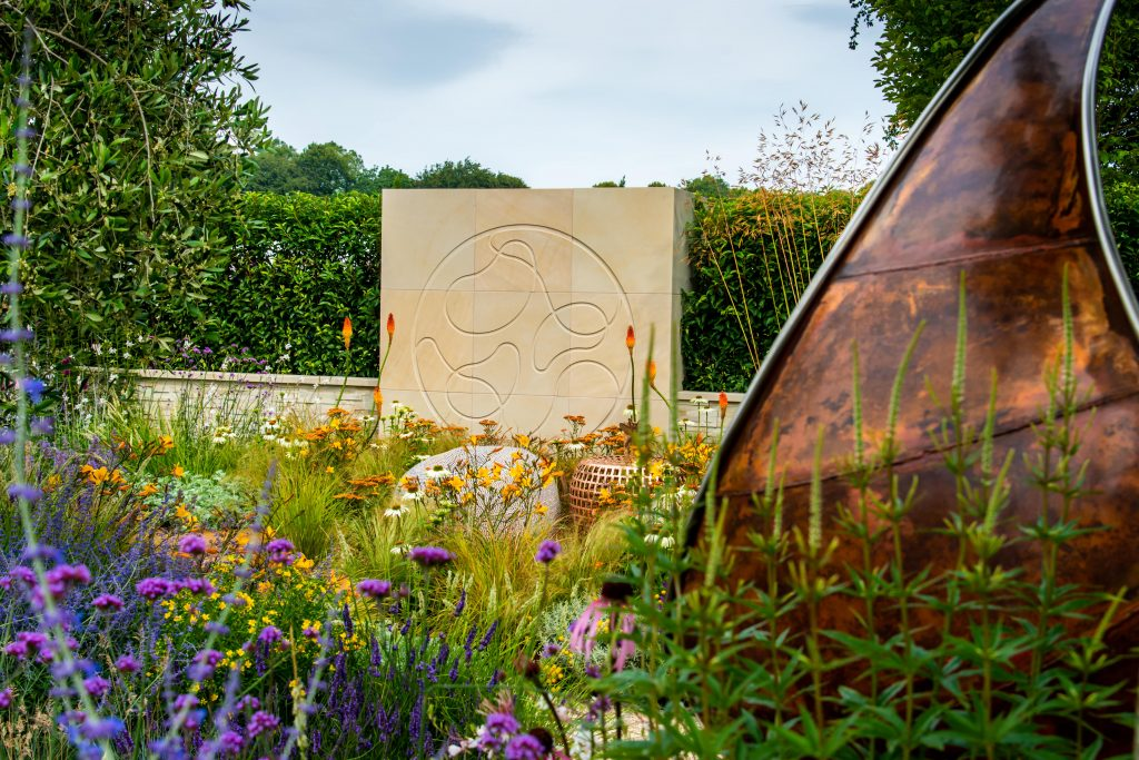 Harvest Sandstone feature wall with engraving with hedges behind, planting in front and metal sculpture.