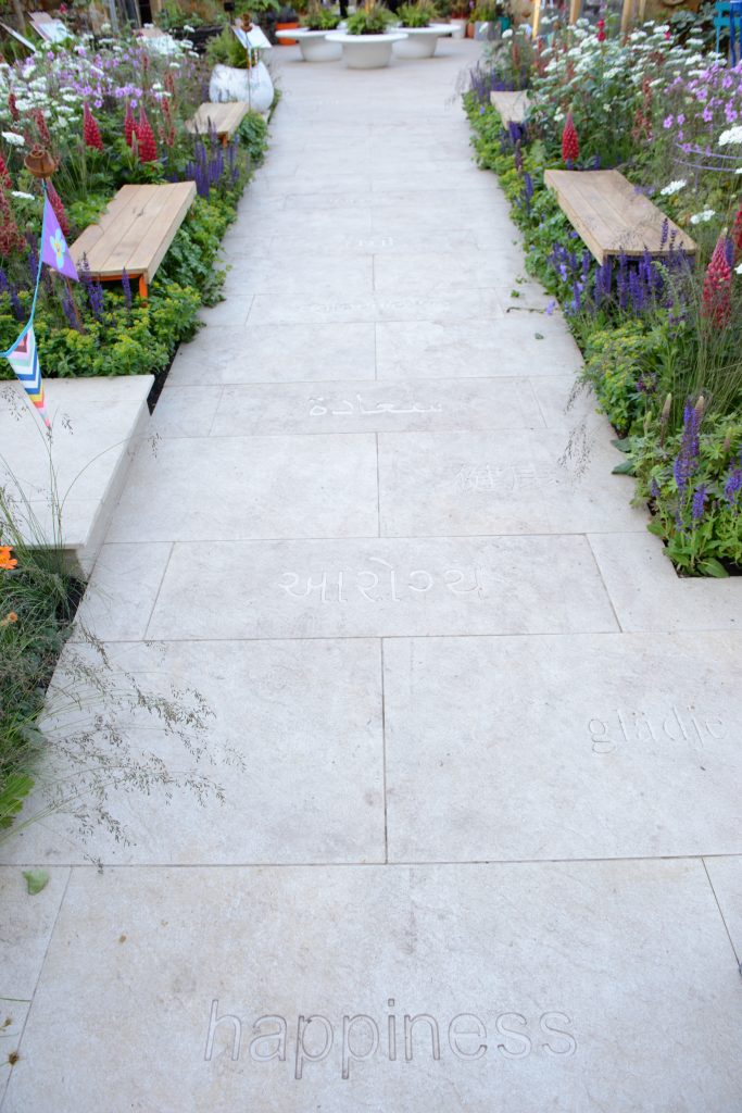 The word happiness is inscribed into Golden Stone Porcelain paving in various languages.