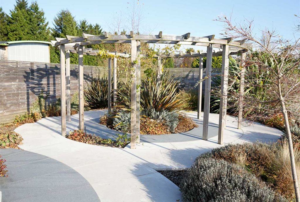 A round pergola with porcelain paving laid in circles in and around it at London Stone's showroom, Cooling's, Knockholt Kent