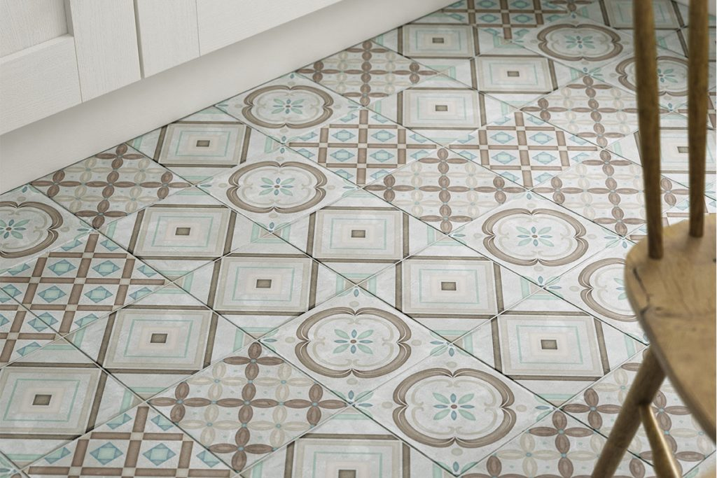A close up of cream, brown, beige and mint mixed print, patterned floor tiles.