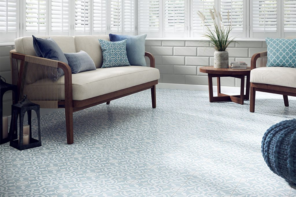 Blue patterned floor tiles are paired with plain grey wall tiles. A plain sofa with blue cushions perfectly complements the tiles.