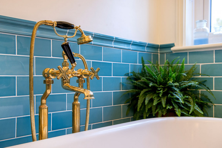 Marine blue gloss tiles splashback with chair rail tile and gold tap fittings from London Stone