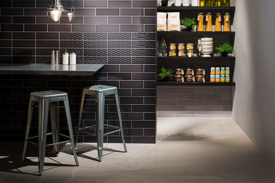 A kitchen wall with Noir gloss British made ceramic tile with band of Decor textured tiles from London Stone
