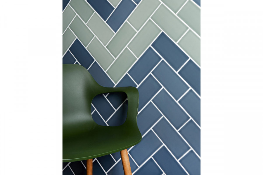 A green plastic chair against a wall of British made ceramic Savoy slate and Sage wall tiles from London Stone