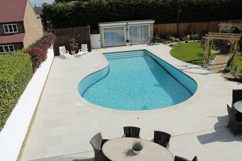 Beige Sawn Sandstone pool surround and paving from London Stone, laid by Timotay Landscapes